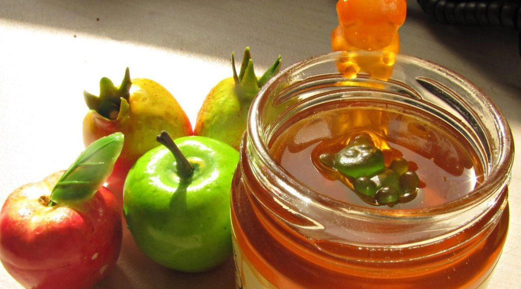 Photo depicting red and green apples along with pomegranates and a jar of honey on a wood-grained table. The jar of honey has a green gummy bear floating in it while a yellow gummy bear looks into the jar at the other.