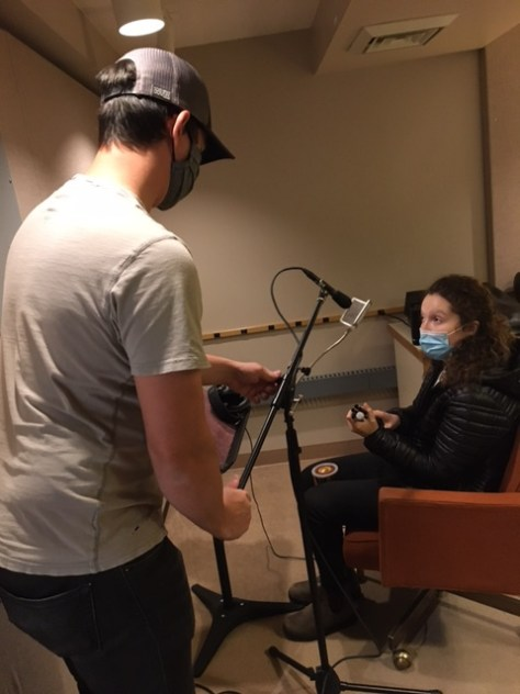 Photo depicting a male-presenting individual assembling a microphone stand in a sound studio. A female-presenting actress with a blue surgical face mask is sitting in an orange chair in front of the microphone.