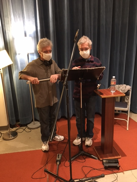 Photo depicting two brothers standing in front of a music stand and microphone stand wearing white surgical face masks in a recording studio.