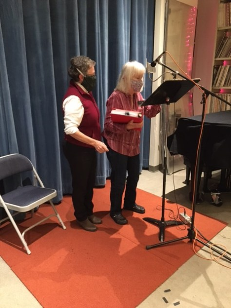 Photo depicting two individuals, one in a red sweater vest and the other in a red-collared shirt, stand in front of a music stand and microphone stand getting ready to record.