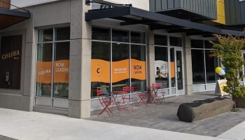 """Photo depicting the retail level of the Colina Apartments building with an orange-waved window sign that reads """"Now Leasing."""" Red folding outdoor chairs and stables sit outside the entrance to the space."""