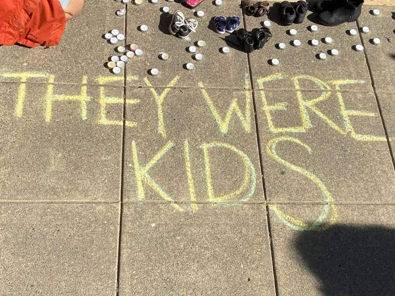 """Photo depicting writing in yellow chalk that reads, """"They Were Kids."""" Candles and babies' and children's shoes surround the writing in the background."""