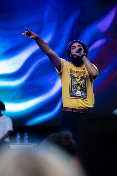 Photo depicting Seattle musical artist Sol singing into a microphone while raising a hand out to the crowd. A blue background displays on the screen behind him.
