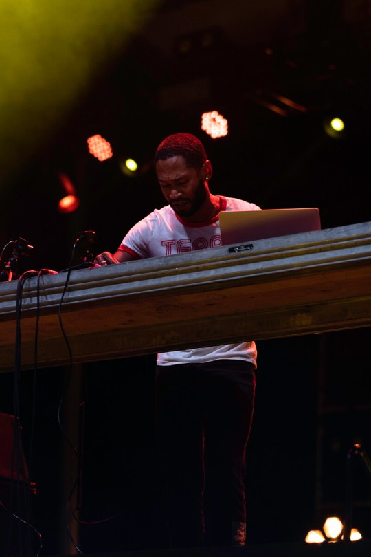 Photo depicting Kaytranada at his DJ set, with stage lights shining down on him as he performs.