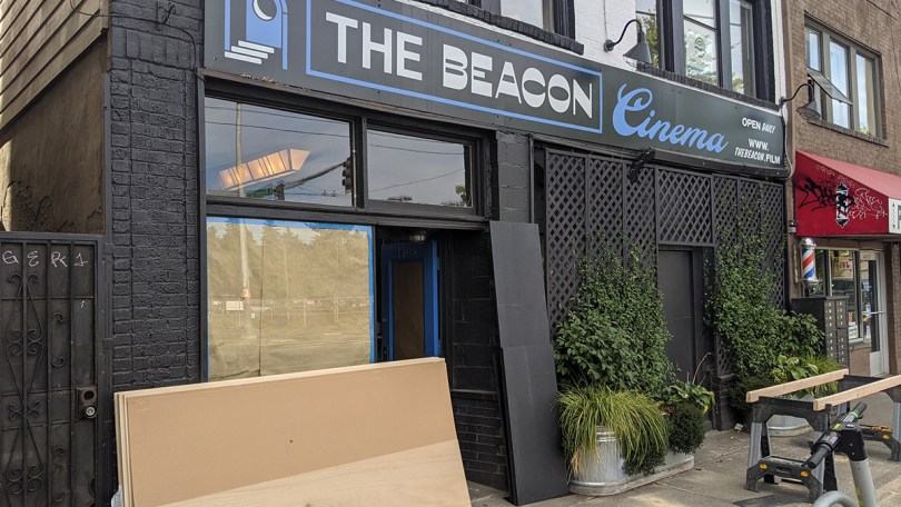 Photo depicting the exterior of The Beacon Cinema, with black walls and doorframe with a blue-and-white text sign.