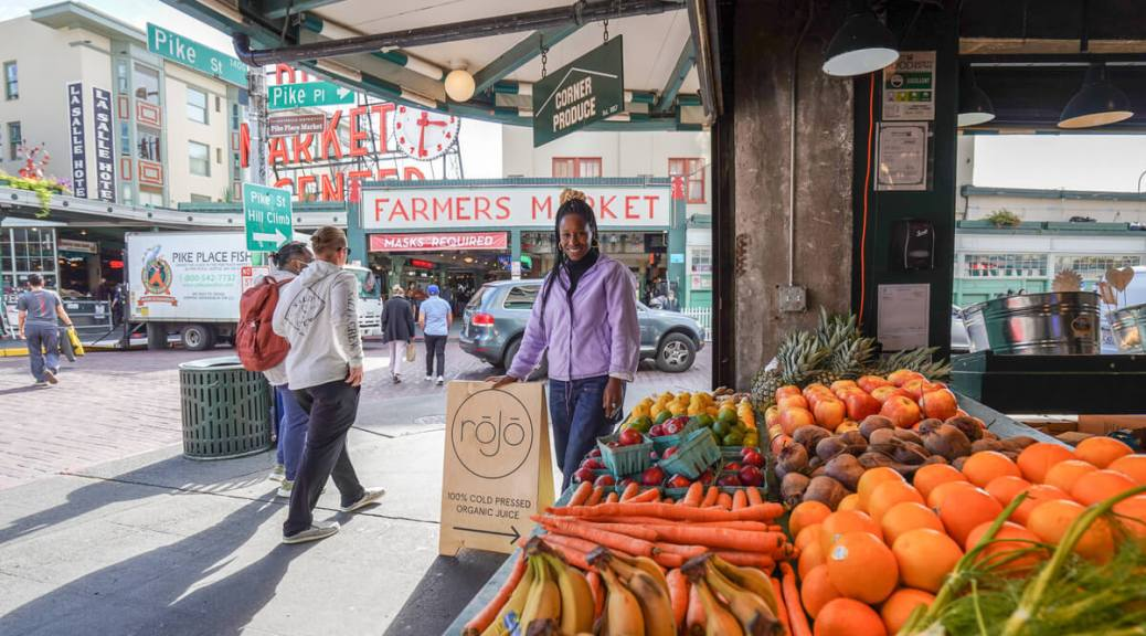 """Photo depicting a Black woman in a lavendar jacket standing at a brightly colored fruit stand with parts of Pike Place Market in the background. The woman has her hand resting on a sign that reads """"rōJō Juice."""""""