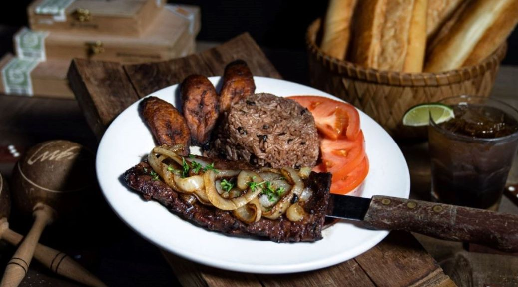 Photo depicting Churrasco Timbero, a 10-ounce Angus prime skirt steak with a side of moros and maduros. A basket of fresh bread and a drink with a lime are in the background.