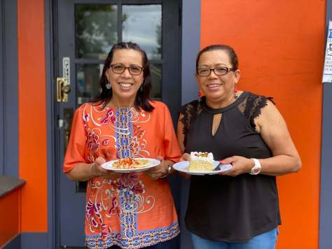 Photo depicting Aminta Elgin and Ana Castro holding delicious Salvadorean dishes outside their bright orange entrance to their bakery.