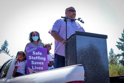 """A man with sunglasses stands at a podium and speaks into a microphone. Someone is holding a sign behind him that says """"Safe Staffing Saves Lives""""."""