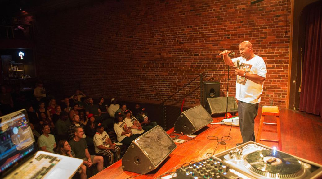 Perspective of someone on a stage watching a Black man on the stage holding a microphone and gesturing with his hand, a brick wall behind him, and A DJ set up in the foreground. The faces of some of the audience members watching the man perform is visible.