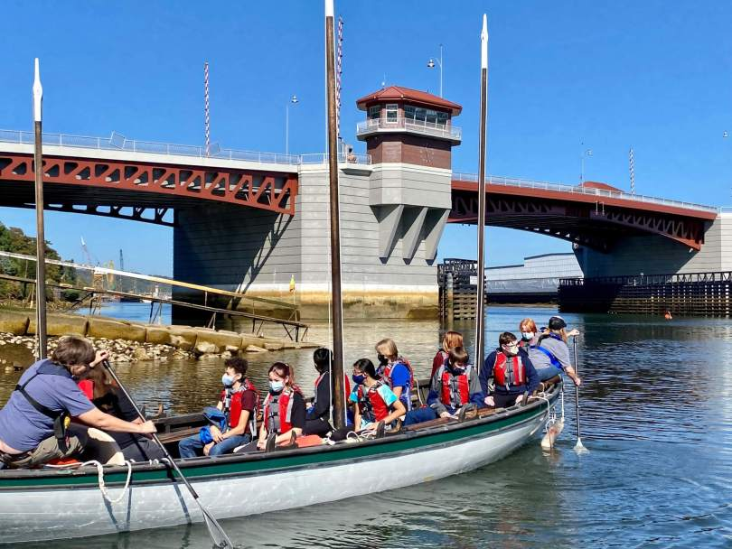 Photo depicting a group of students wearing red life jackets and their instructors in a long rowing boat on a river.