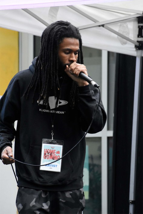 Photo depicting AJ Suede rapping into a microphone.
