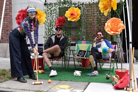 Photo depicting a female-presenting individual in a colorful outfit posing with a croquet mallet while in the background two male-presenting individuals sit on colorful lawn chairs.