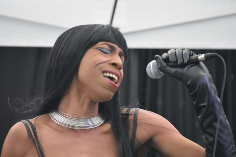 Photo depicting Ade Connere singing into a microphone.