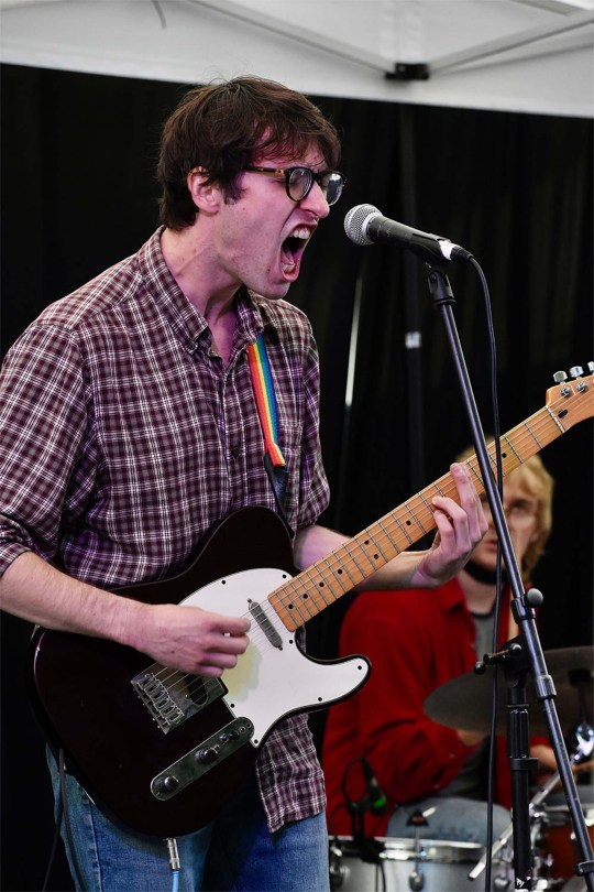 Photo depicting a band member of Bread Pilot singing into a microphone.