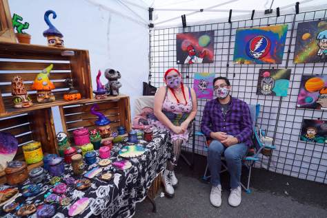 Photo depicting two individuals sitting inside an art and sculpture booth at an outdoor flea market.