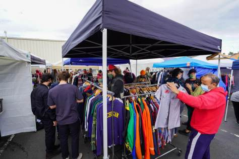 Photo depicting shoppers milling around clothing racks at an outdoor flea market booth.
