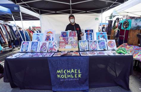Photo depicting Michael Koehler with his prints at his booth at an outdoor flea market.