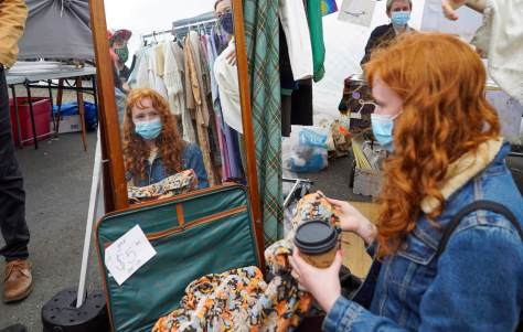 Photo depicting a female-presenting individual with red hair looking at a dress in a mirror at an outdoor flea market.