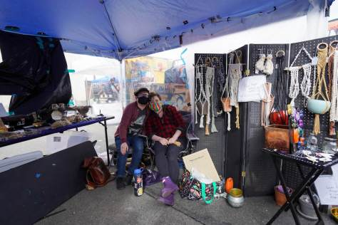 Photo depicting Jaye Zehring and Ansel Letourneau sitting beside their wares at an outdoor flea market.