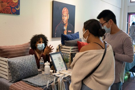 Photo depicting Eva Hutchins wearing a blue surgical face mask sitting behind her booth featuring home products from In Her Threads speaking with event attendees