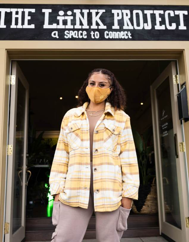 Photo depicting Stephanie Morales standing at the entrance of The Liink Project, wearing a mustard-yellow cloth face mask and a coordinating yellow plaid shirt.