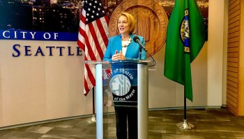 Photo depicting Seattle Mayor Jenny Durkan speaking at a podium during a press conference wearing a bright blue blazer at Seattle City Hall.