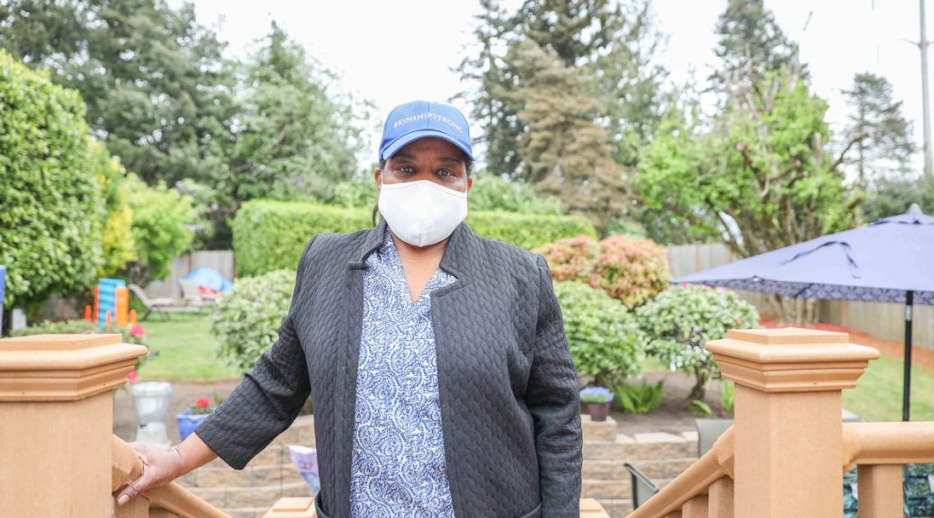 """Photo depicting Alesia Cannady in a blue-grey cardigan, blue-patterned top, blue baseball cap that reads in white text """"#KinshipStrong,"""" and white facemask standing at the top of stairs leading to her Skyway home's backyard."""