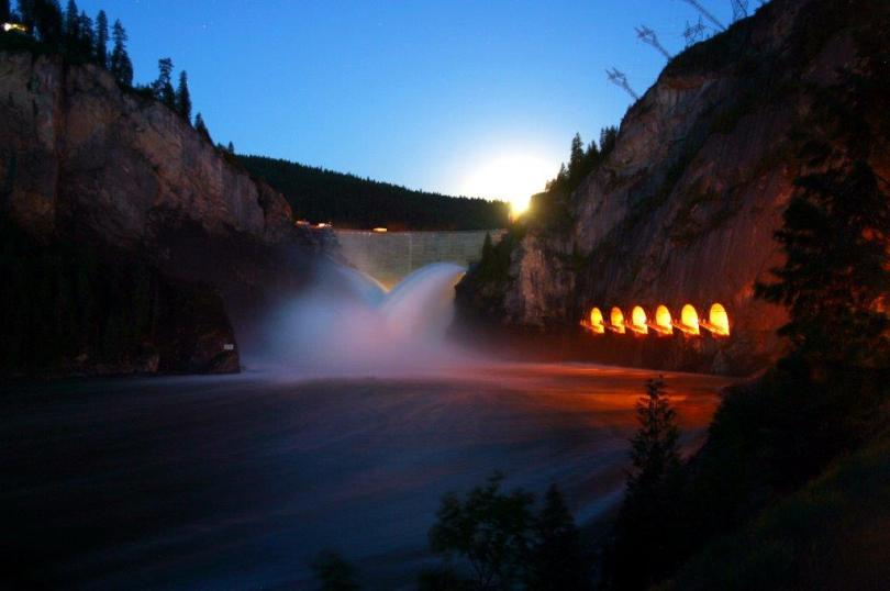 Photo depicting the Boundary Hydroelectric Project dam at night with the lights reflecting off the lake as water falls through the dam.