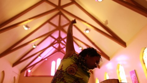 Film still depicting a Black-presenting individual with a first raised toward a church ceiling.