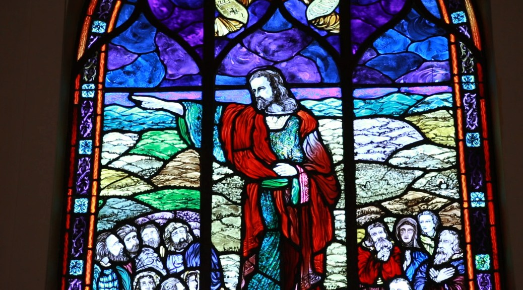 Film still depicting a stained glass Jesus pointing westward.