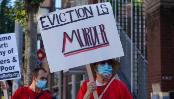 """Photo depicting protestors in bright red shirts carrying signs that read, """"Eviction is Murder."""""""