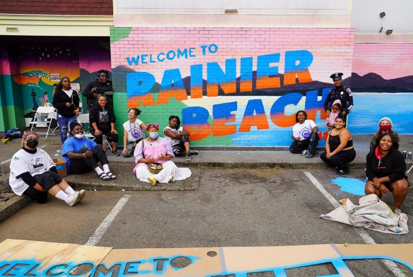 """Photo depicting various individuals standing or sitting in front of a brightly colored mural on a brick wall that reads, """"Welcome to Rainier Beach."""""""