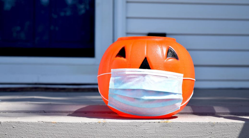 Photo depicting a Halloween jack o lantern wearing a covid-19 face mask and placed outside a home at daytime. House, front door, and window visible in background.