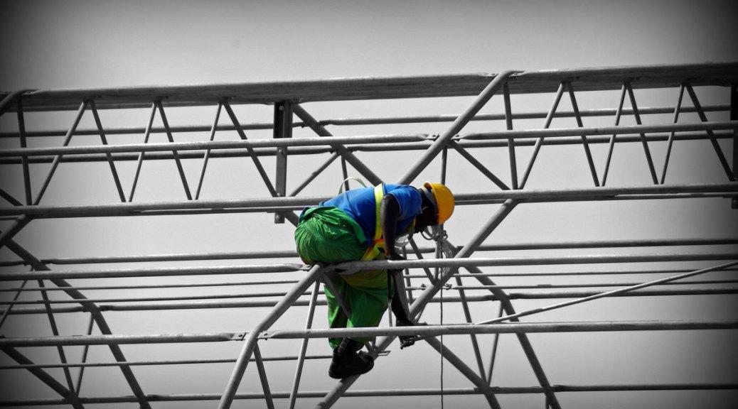 Photo depicting a construction worker building along a construction rail.