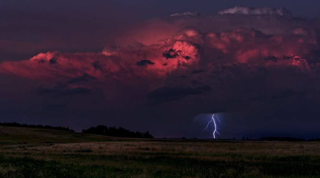 Photo depicting an evening thunderstorm with dark red thunderclouds in a dark purple sky and a lightning striking an open field.