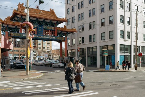 Photo depicting a pair of individuals walking toward Seattle's Chinatown-International District gate/archway.