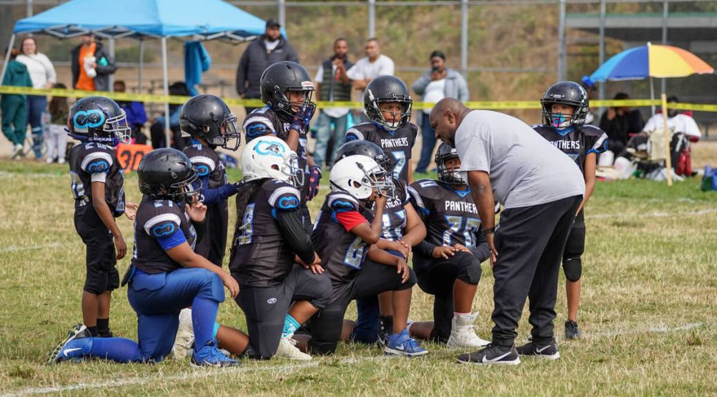 Photo depicting Black-presenting youth football players huddled by their coach who is giving advice/instructions.