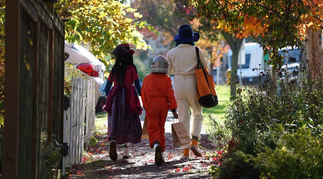 Trick-or-treaters walking away from the camera down an autumnal street.