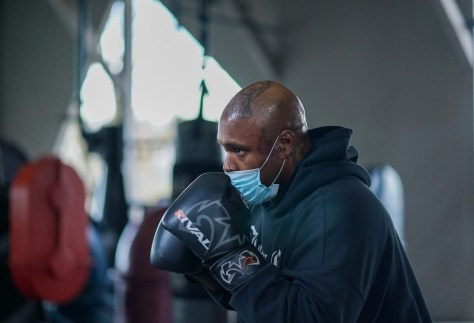 Photo depicting Jordan Carter in boxing gloves and a blue surgical face mask in a boxing stance.