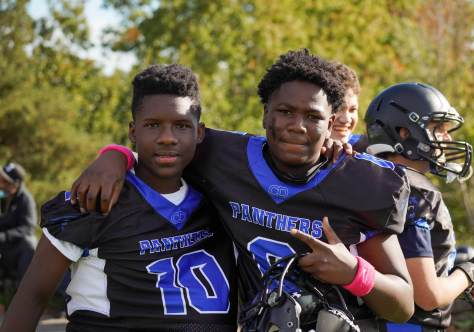 Two CD Panther players smile and pose in front of the camera as they wait to take the field.