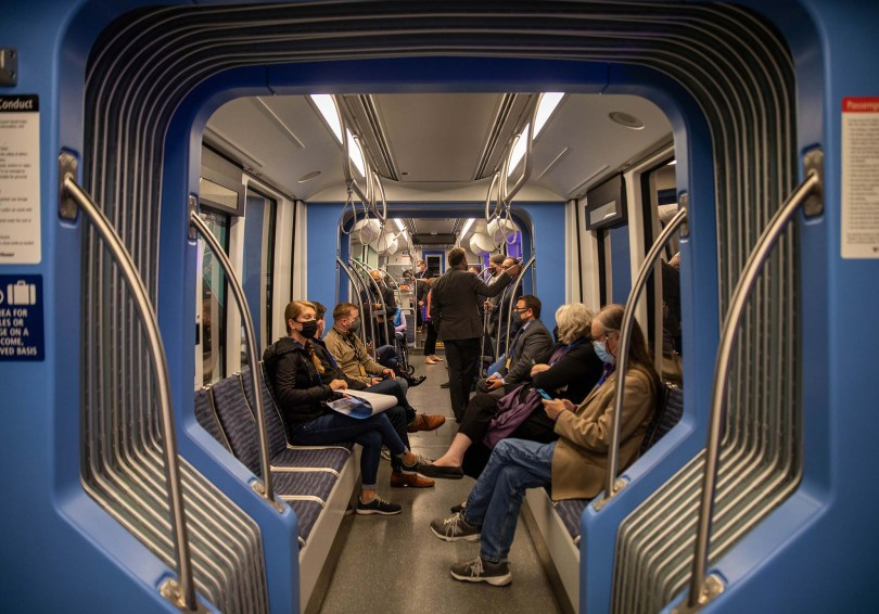 Photo depicting the interior of a new Link light rail train car with various riders seated and standing, all wearing face masks.