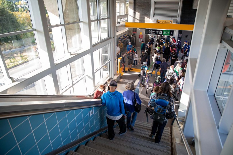 Photo depicting light-rail riders taking an escalator down into the ground-floor level of Northgate Station.