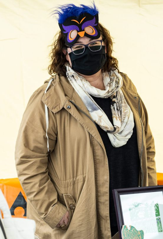 Photo depicting Renee C. Look wearing a black surgical face mask and a black-and-purple owl eye mask sitting atop their forehead.