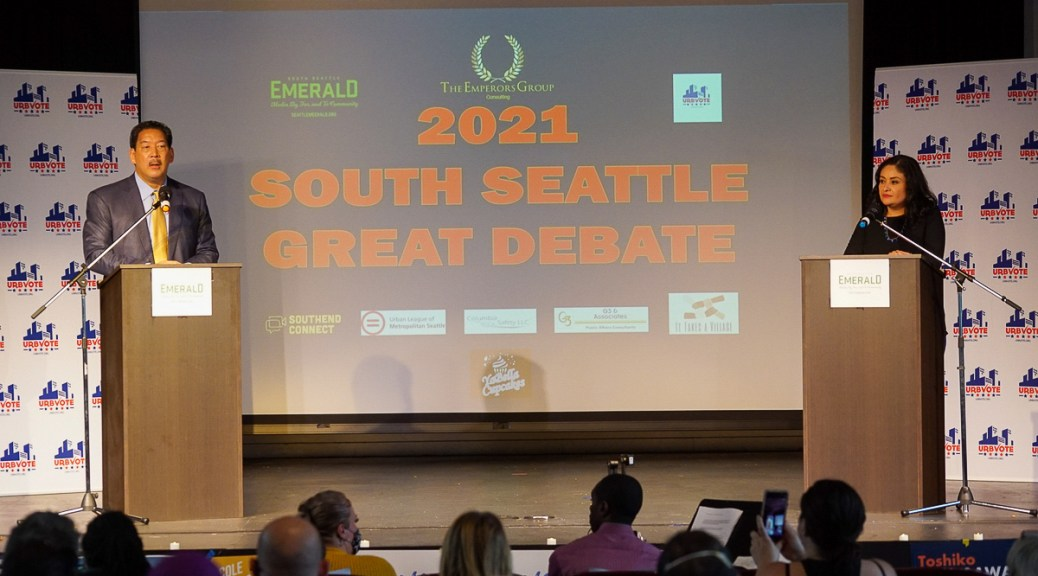 """Photo depicting the 2021 Seattle mayoral candidates Harrell and Gonzalez debating on the Rainier Arts Center stage with a banner that reads """"2021 South Seattle Great Debate"""" in orange text on a blue background behind them."""