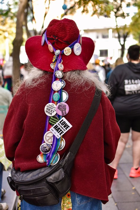 Photo depicting the back of a protestor wearing red and a red hat with a rainbow ribbon covered in social justice pins.