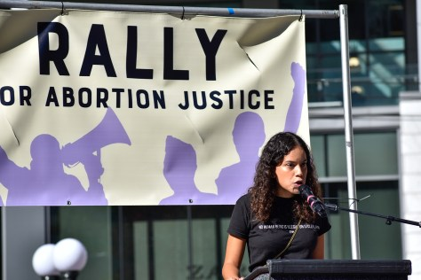 """Photo depicting Graciela Nunez speaking into a microphone at a podium, a banner that reads """"Rally for Abortion Justice"""" hangs behind her."""