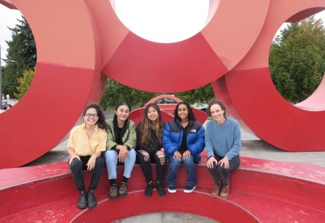 Photo depicting a group of individuals sitting on a red sculpture.