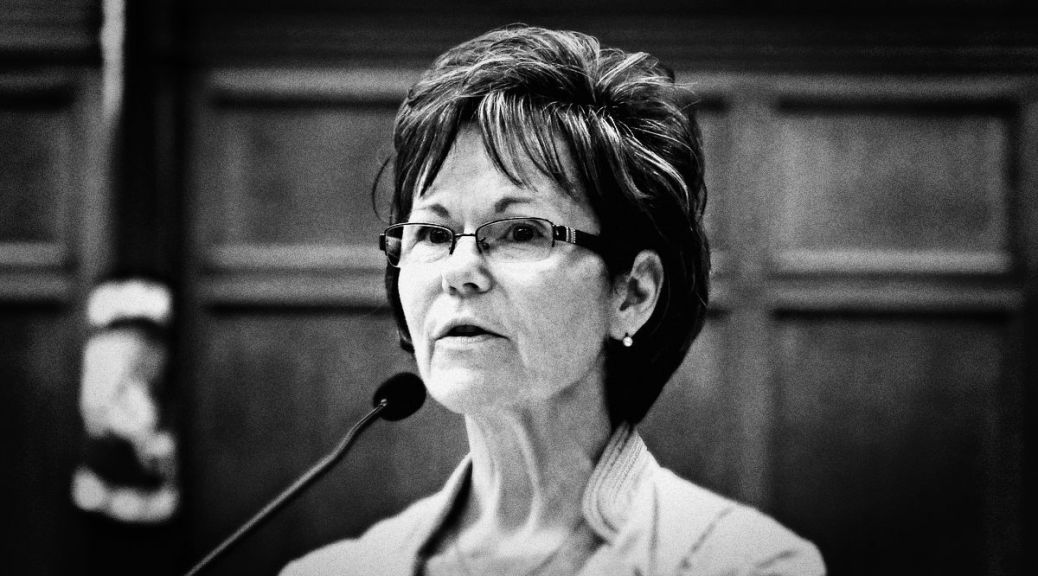 Black-and-white photo depicting Kathy Lambert speaking into a microphone.
