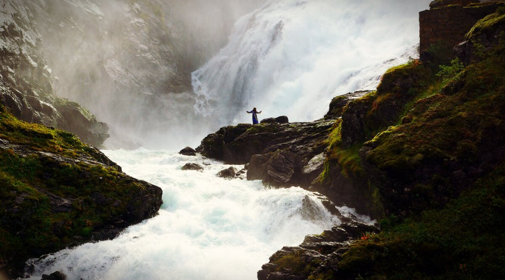 Photo of a rushing river flowing away from a waterfall in the background. Rocky hills reach in from each side. Just in front of the waterfall, a figure stands with arms outstretched. Photo by Aleksey Fefelov/Shutterstock.com. Photo editing by Emerald Staff.